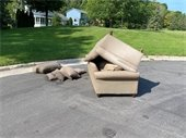 Old broken couch and cushions dumped in middle of street