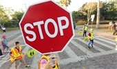 Crossing Guard holding Stop sign as kid's cross the street