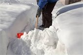 Person shoveling deep snow on sidewalk