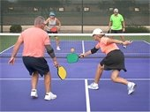 4 people playing pickleball