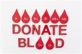 """""""Donate Blood"""" in red with blood drops surrounding - each with a different blood type on it"""