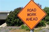 Road Work Ahead sign near bridge